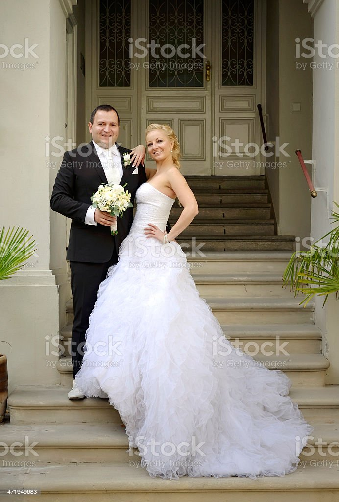 Newlywed couple posing on stairs royalty-free stock photo