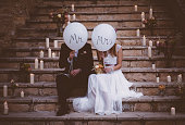 Newlywed couple sitting on steps and holding balloons