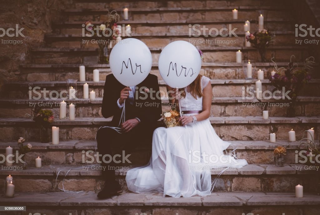 Newlywed couple sitting on steps and holding balloons stock photo