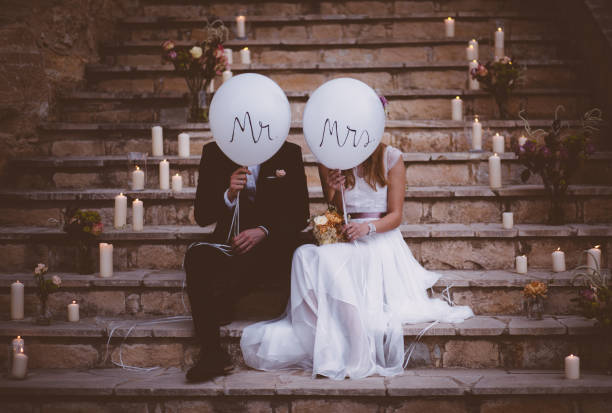 newlywed couple sitting on steps and holding balloons - wedding stock pictures, royalty-free photos & images