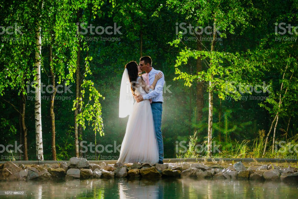 Newlywed couple standing next to a pond in the rain stock photo