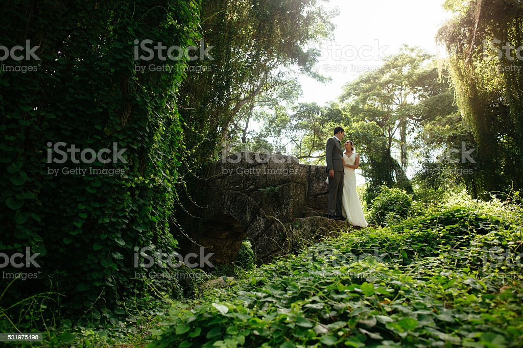 Newlywed couple together in a tropical forest stock photo
