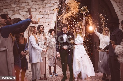 Newlywed bride and groom leaving church and celebrating wedding with guests throwing flowers and rice