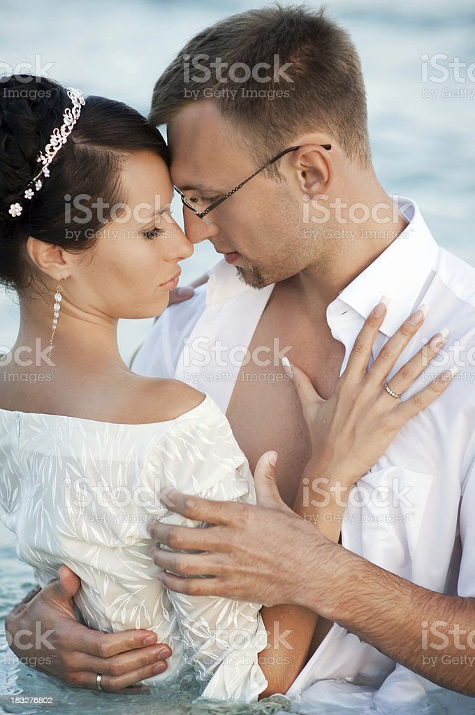 Newlywed embracing in the water. stock photo