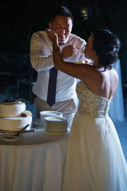 Newlywed feeding each other cake Bride and groom celebrating at reception chinese wedding dinner stock pictures, royalty-free photos & images