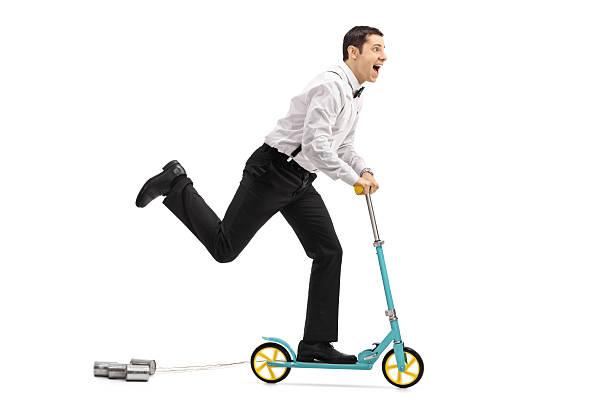 newlywed groom riding a scooter - zinn hochzeit stock-fotos und bilder