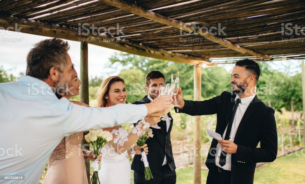 Newlyweds and friends having wedding toast stock photo