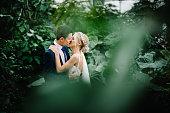 Newlyweds are standing and kissing in the Botanical green garden full of greenery. Wedding ceremony.