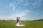 newlyweds are walking along the green field of the golf club on a wedding day. The groom in a business suit is gray and the bride in a luxury white dress with a veil are holding hands