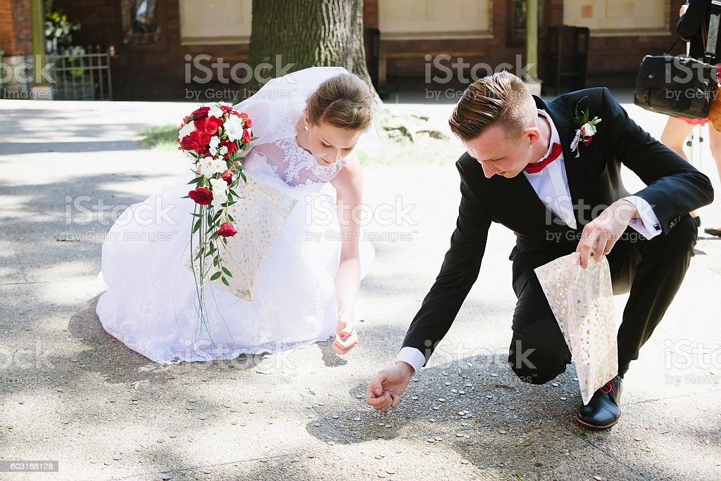 Newlyweds collects coins thrown by the wedding guests. stock photo