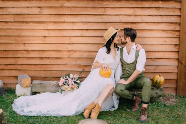 newlyweds dressed in boho style sit near wooden wall stock photo