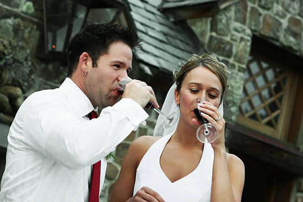 paar trinken nach der hochzeit anstoßen - rot bekümmerte möbel stock-fotos und bilder