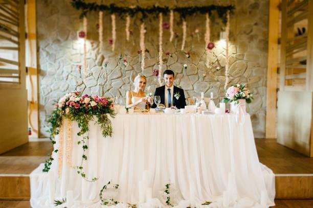 brautpaar gläser champagner der holding die drinnen. hochzeit zeremonie dekoriert mit blumen und grün. braut und bräutigam am tisch im festsaal des restaurants. - bräutigam tisch stock-fotos und bilder