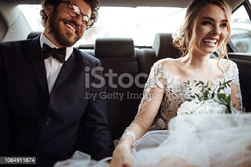Newlyweds holding hands in the backseat