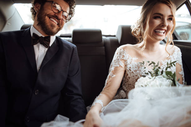 Newlyweds holding hands in the backseat Newlyweds holding hands in the backseat bridegroom stock pictures, royalty-free photos & images