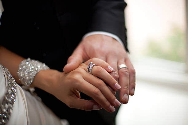 newlyweds holding hands - diamond ring hand stock photos and pictures