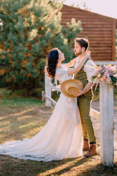 Newlyweds in cowboy style standing and hugging on ranch stock photo