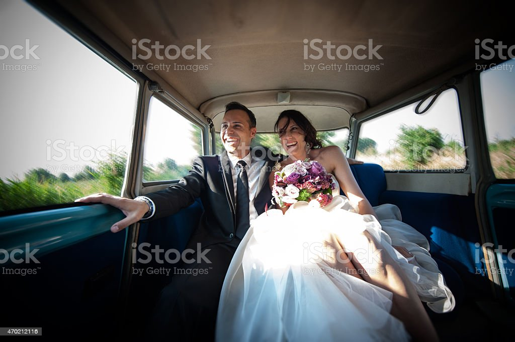 Newlyweds in wedding car stock photo