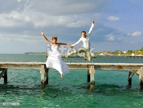 Newlyweds jumping of a dock shortly after saying their vows in the Caribbean