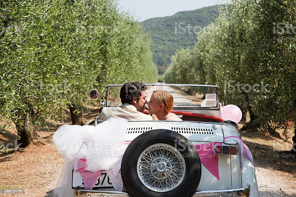 Newlyweds kissing in classic car stock photo