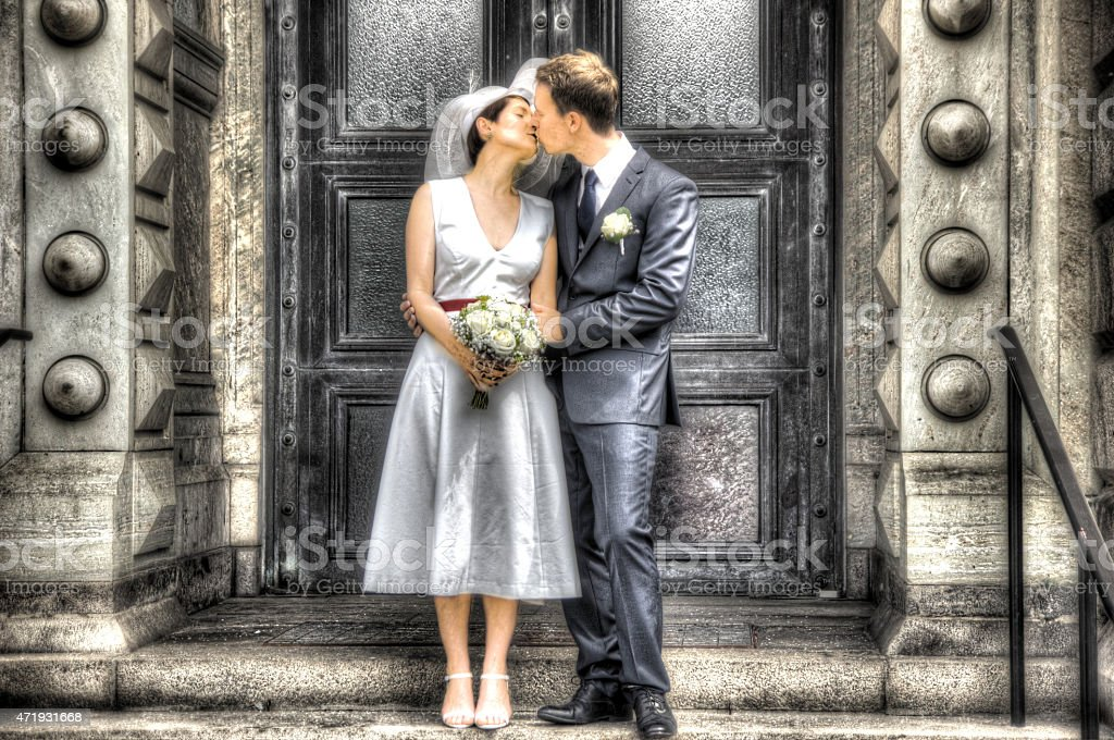 Newlyweds Kissing outside a church, painting effect stock photo
