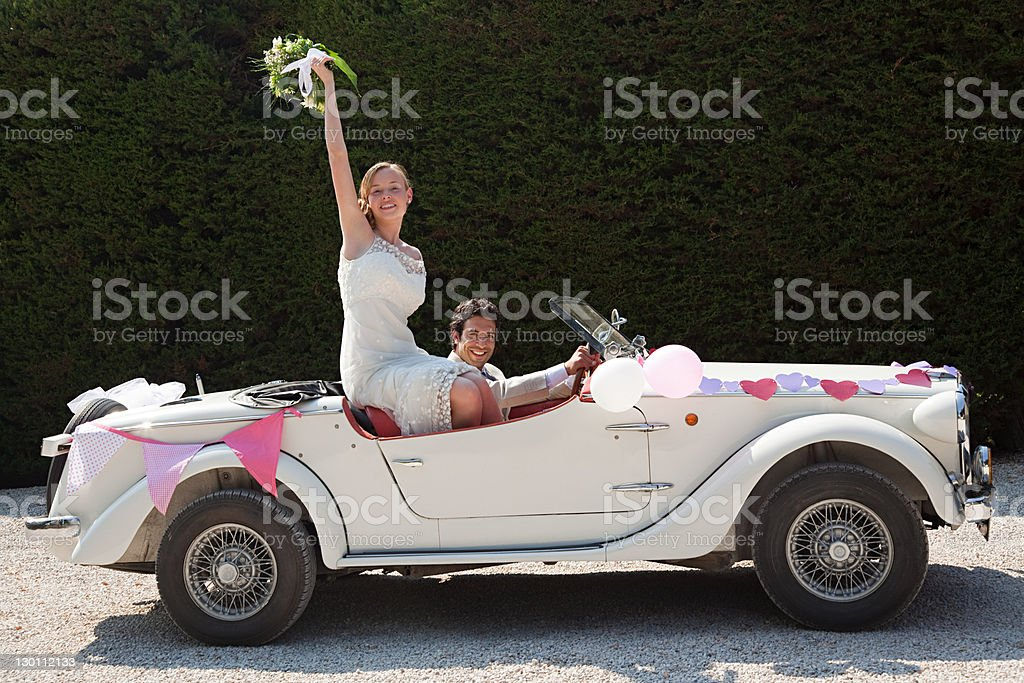 Newlyweds leaving for honeymoon in vintage car stock photo