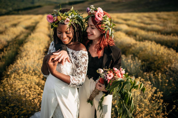 Newlyweds Lesben umarmen sich im Blumenfeld – Foto