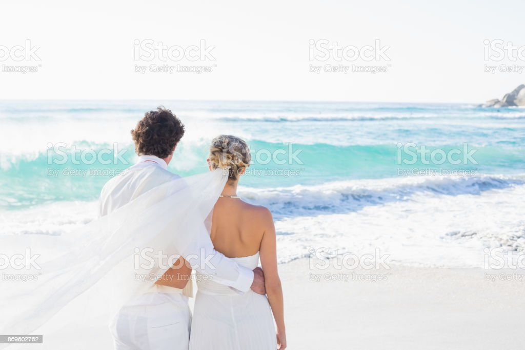 Newlyweds looking out to sea together stock photo