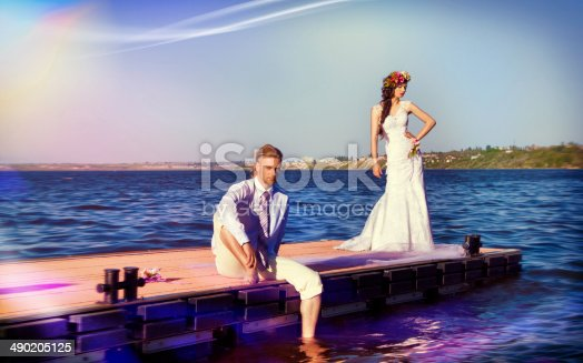 674214372istockphoto newlyweds on a pier against blue water 490205125