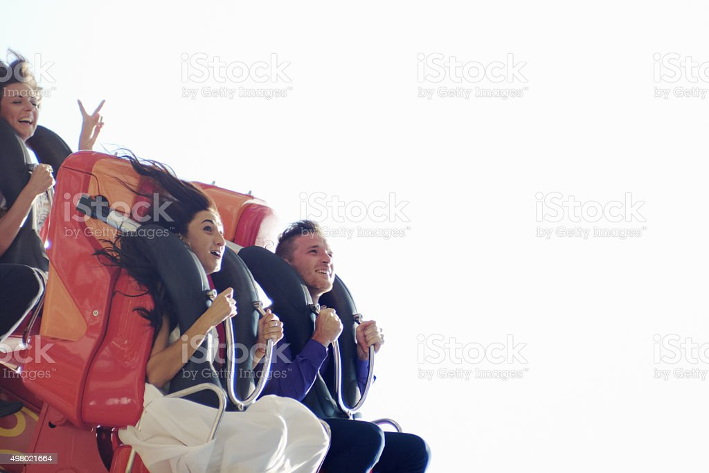 Newlyweds on roller coaster stock photo