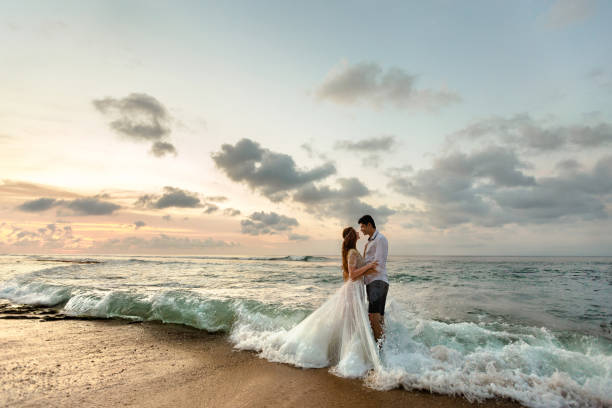 Newlyweds on the beach at sunset Bride and groom hugging on the beach standing in the sea water wedding stock pictures, royalty-free photos & images
