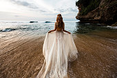 Bride in a white wedding dress comes into the sea water on the beach