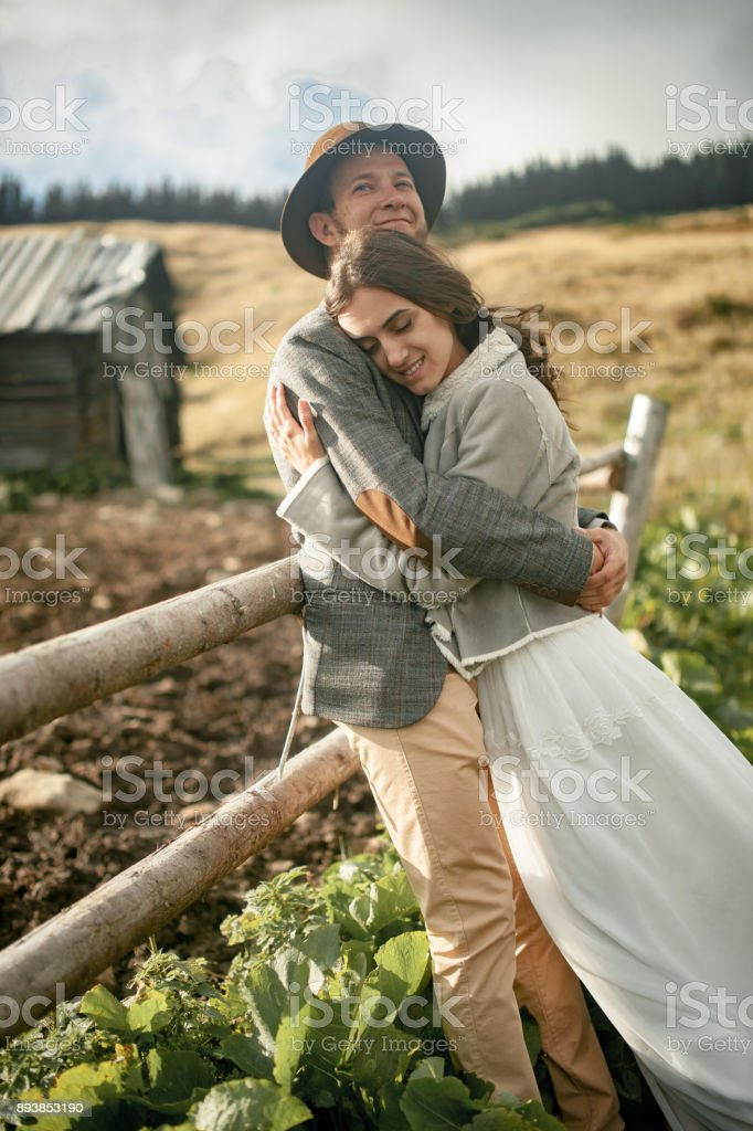 Newlyweds stand, smile and hug background of old wooden hut and fence in Carpathian mountains. Closeup. stock photo