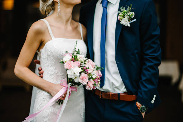 Newlyweds standing and holding bouquet of pink and purple flowers and picture id960620780?b=1&k=6&m=960620780&s=612x612&w=0&h=lzdb17vdvglwddcplgyo 4e5g2v1syhcnsh2aiiwmik=