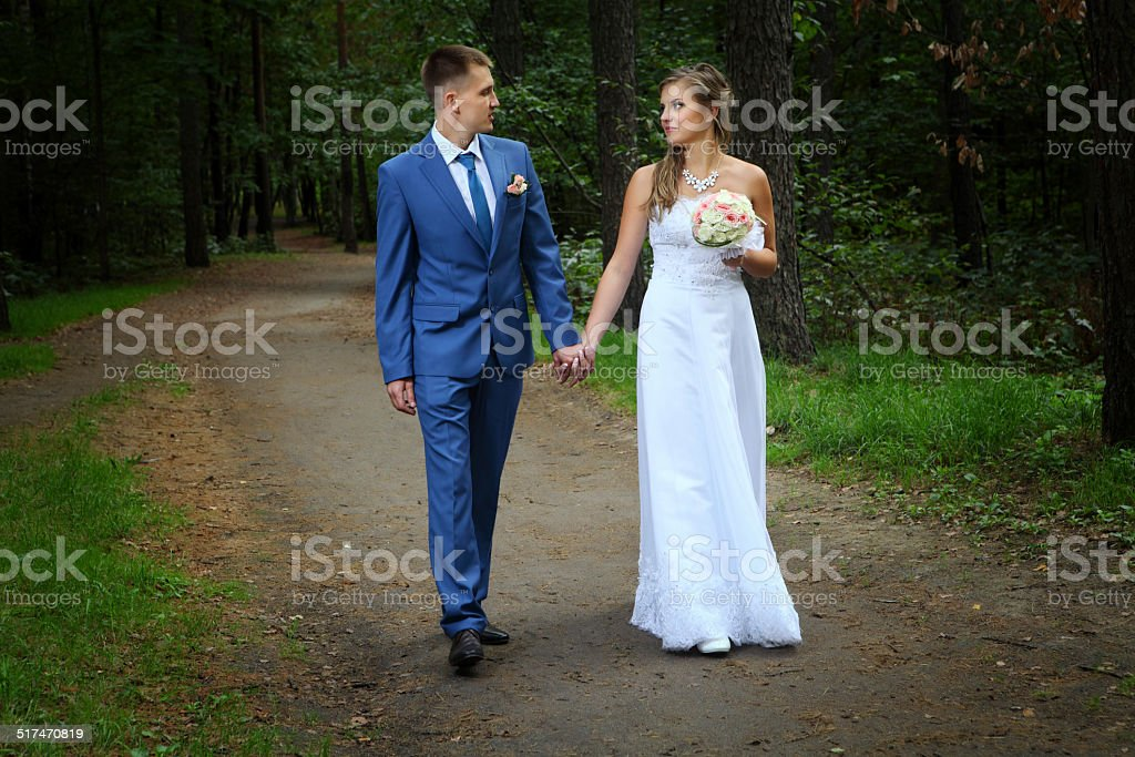 Newlyweds walking along the garden path holding hands stock photo