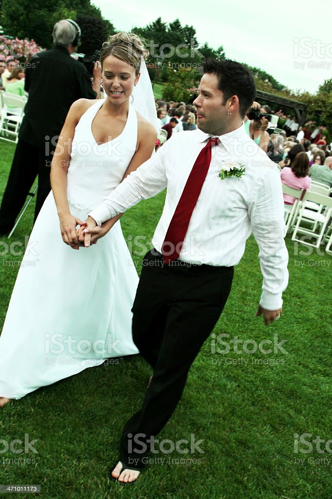 Newlyweds Walking Away from Ceremony royalty-free stock photo