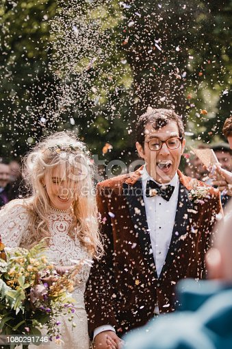A front view shot of a newlywed couple arm in arm, they are walking down the aisle together on their wedding day, confetti can be seen falling around them as they celebrate their special day.