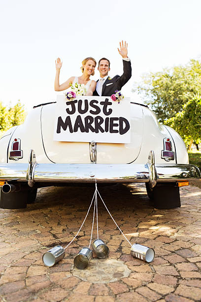 newlyweds waving in convertible car with cans attached to it - pas getrouwd stockfoto's en -beelden