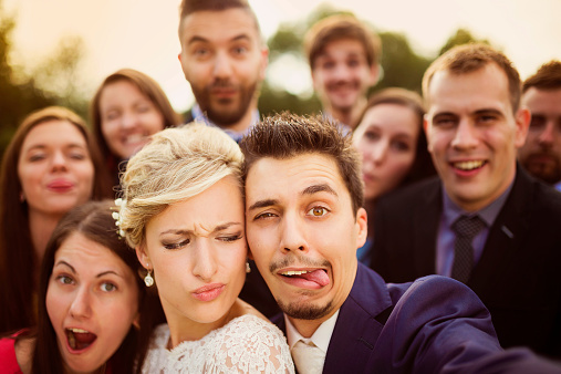 istock Newlyweds with friends taking selfie 517173181