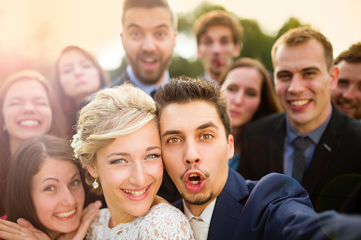 istock Newlyweds with friends taking selfie 517186529