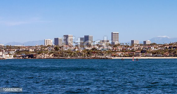 Newport Beach California city skyline on a sunny day with snow capped San Gabriel mountains ghosting in the background, with entrance to the harbor and Corona Del Mar state beach in the foreground