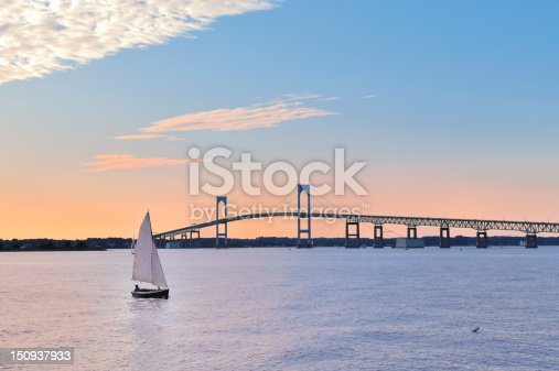 Newport Sunset with Newport Bridge sailboats Newport, Rhode Island, USA. The person in the sailboat is in silhouette & I also changed the shape of the face, body, color of clothing, and hair.