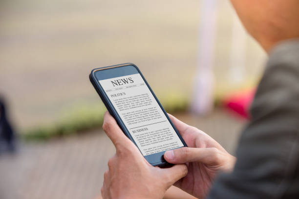 News article concept on phone screen. Man holding smartphone reading news article on screen. stock photo