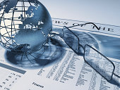 Wireframe earth showing Europe and Africa and glassses standing on the pages of a finance newspaper. High resolution 3D rendering. Numbers and the text on the newspaper are fictious.