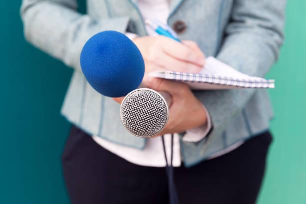 Nachrichtenreporter oder TV-Journalist bei Pressekonferenz, Mikrofon halten und Notizen schreiben – Foto