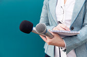istock News reporter or TV journalist at press conference, holding microphone and writing notes 1209659465