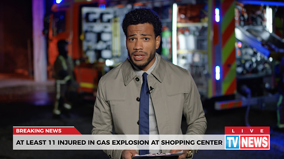 Male news reporter reporting on gas explosion at shopping centre during night.