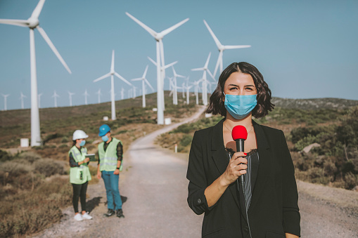 Cameraman and journalist wearing medical face masks. TV news reporters are making reportage about renewable energy systems during virus epidemic against young engineers and wind turbine power generation station.
