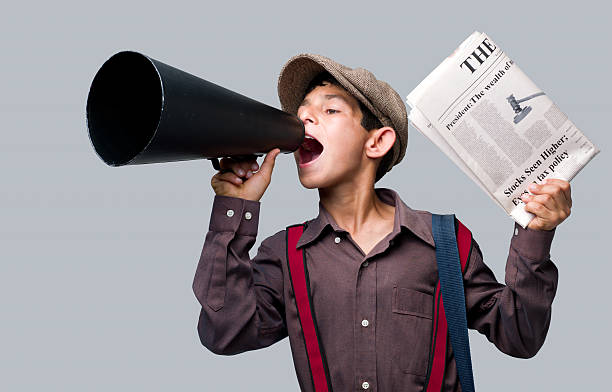 newsboy holding newspaper and shouting to sell - 1920s style stock photos and pictures