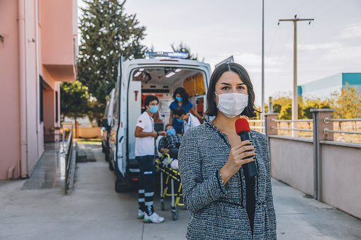 Journalist and TV news reporter young woman wearing a prevention facemask speaking and presenting the breaking news into a microphone during broadcast and making reportage about a Covid-19 virus epidemic in front of a hospital and ambulance staff. Interviewed people during coronavirus quarantine and lockdown.